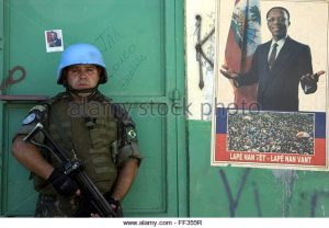 a-un-brazilian-blue-helmet-stands-guard-next-to-a-pro-aristide-poster-ff355r